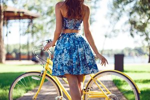 View from the back of a slender young woman in a blue dress with an yellow bicycle