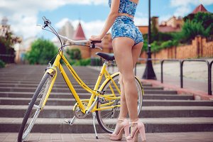 Close up shot of young sexy girl with long nice legs posing with yellow bicycl