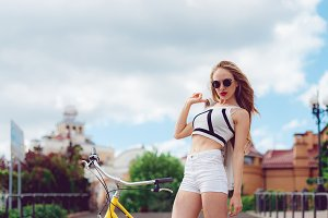 Beautiful blonde girl in white shorts posing sitting on a vintage yellow bike