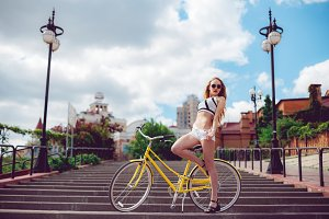 Active fashionable blonde woman posing near a vintage bike