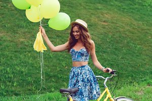 Young sexy woman in blue dress with balloons and retro bicycle posing in the park