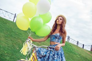 Portait of beautiful woman wearing a nice blue dress having fun in park with bicycle