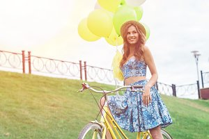 Happy girl posing on yellow bicycle with ballons and smiling.