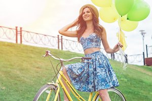 Beautiful young woman riding bicycle with hat on her head enjoying summer time