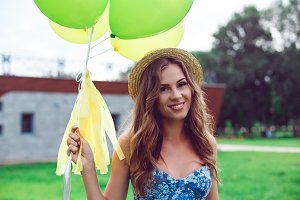 Portrait of a beautiful smiling woman in a straw hat holding balloons