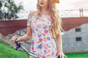 Portrait of beautiful blonde girl riding bike in park