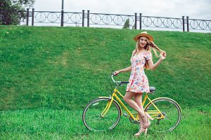 Full length portrait of a beautiful blond woman posing near a yellow bicycle on a green lawn park