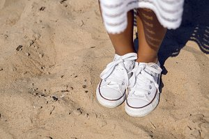tanned legs in sneakers standing on the sand
