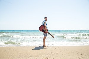 young man with acoustic guitar on the beach