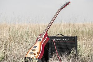 electric guitar and amp on the field, the concept of music