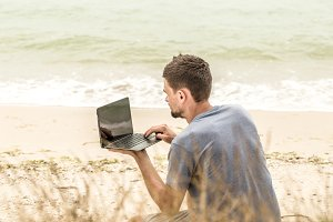 man running on the computer, to work on the beach