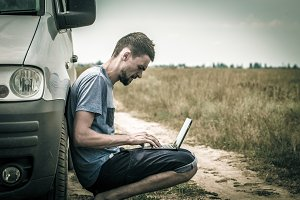 man running on the computer, in nature near the car