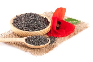Poppy seeds in a wooden bowl with a flower on sackcloth