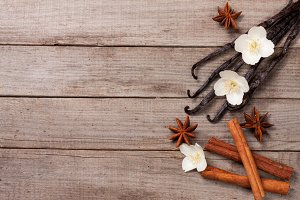 Vanilla sticks with cinnamon and flower on a old wooden background with copy space for your text. Top view