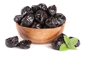 Dried plums or prunes with a mint leaf in wooden bowl isolated on white background