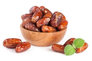 Dates in a wooden bowl with a mint leaf isolated on white background