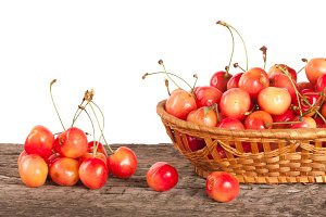 Yellow cherry in a wicker basket on a wooden table with a white background