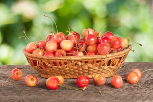 Yellow cherry in a wicker basket on a wooden table with a blurry garden background