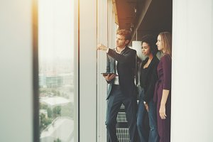 Three business persons near window
