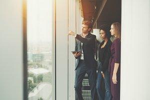 Three business persons near window