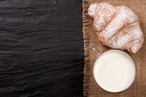 glass of milk with croissants on black stone background with copy space for your text. Top view