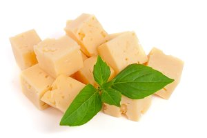 cheese cut into cubes with basil leaves isolated on white background