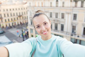 Cute sexy girl with brown hair stands on the roof of the house in the old town and makes a selfie on your smartphone. Stylish woman smiling at the camera