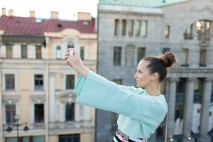 Cute sexy girl with brown hair stands on the roof of the house in the old town and makes a selfie on your smartphone