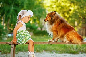 Little girl and dog sitting on bench
