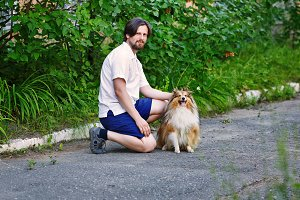 Man in park with his pet Sheltie dog