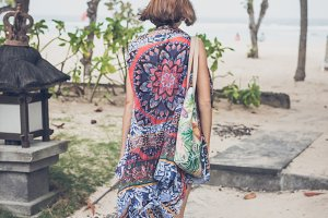 Freedom concept. Young woman in pareo and swimsuit with beach bag entering the beach. Tropical island Bali, Indonesia.