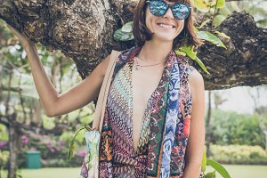 Sexy young brunette woman in pareo and sunglasses posing near the tree in Nusa Dua park of Bali island, Indonesia..Fashion summer photo..