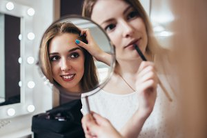 Young female client looking in the mirror while makeup artist working on her eyebrows in beauty salon