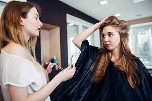 Hair stylist working on female customer s hairdo clipping strands with hair pins in hairdressing studio