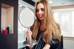 Portrait of happy young woman looking in the mirror sitting in a beauty salon