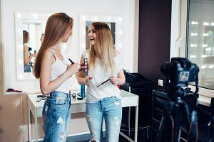 Two young female bloggers recording makeup tutorial on camera in beauty shop