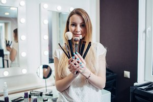 Portrait of young make-up artists showing her brushes looking at camera in beauty studio