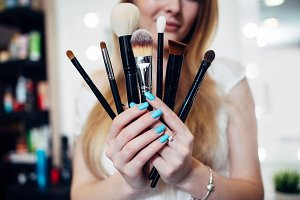 Close-up image of female hands holding a set of make-up brushes