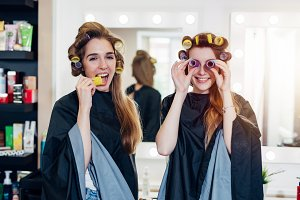Two funny young girlfriends in hair curlers wearing capes having fun time together in beauty salon. Female friends fooling around with rollers, making faces
