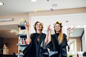 Two female customers of beauty salon standing in hair rollers having fun playing laughing