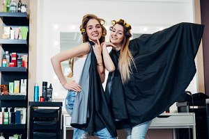 Portrait of two pretty blondes wearing hair rollers and cape standing in funny silly pose looking in camera at hairdressing and beauty studio