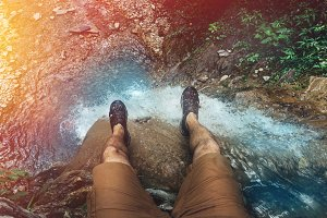 Male traveler's feet on the top of a waterfall on the background of the mouth of a mountain river. Gelendzhik, Russia