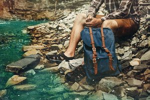 Unrecognizable  young tourist with a backpack, stopped for a vacation near a mountain river overlooking the waterfall