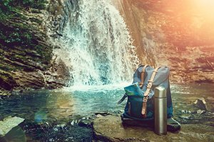 Hipster Blue Backpack, Map And Thermos. View From Front Tourist Traveler Bag On Waterfall Background