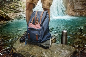 Adventure Hiker Man Feet, Backback And Thermos On Waterfall Background