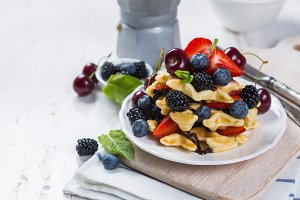 Breakfast - waffles with berries on white plate