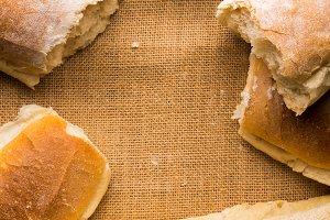Freshly baked bread on burlap dark wooden background