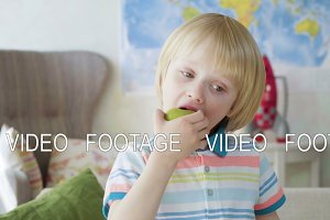 small kid boy bite juicy fresh green apple as a healthy snack wishing to be strong and active
