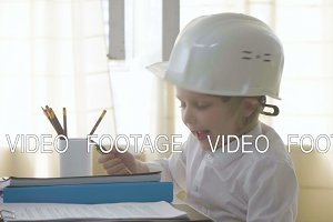 small kid boy in white helmet imitates constructor working and busy man