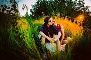 guy and the girl sitting on a background of grass